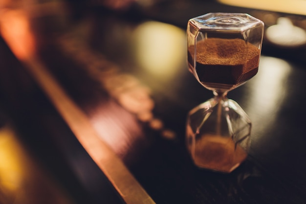 Hourglass with falling sand inside a glass bulb
