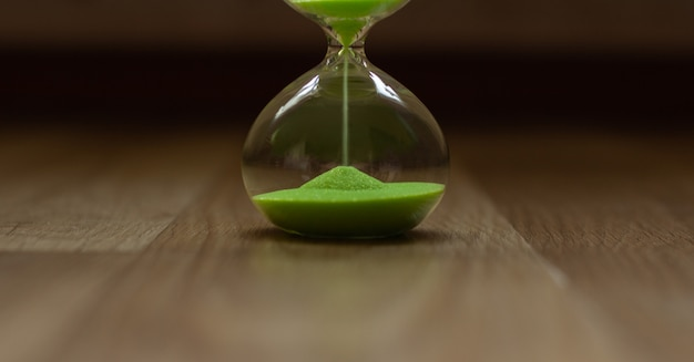 Hourglass with green sand, the lower part of the clock
