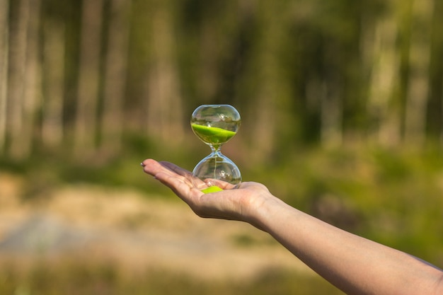 Hourglass with green sand on the palm of the girl on a blurred background
