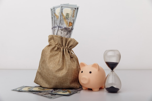 Hourglass with money bag on white background investment and savings concept