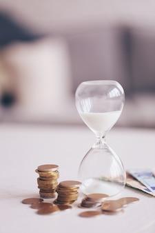 Песочные часы с деньгами на столе на яркой поверхности
