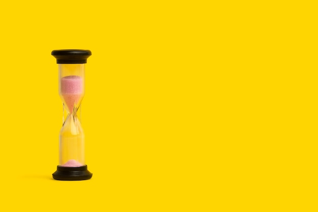A hourglass with pink sand with copy space