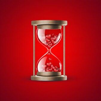 Песочные часы с красным сердцем на красном фоне