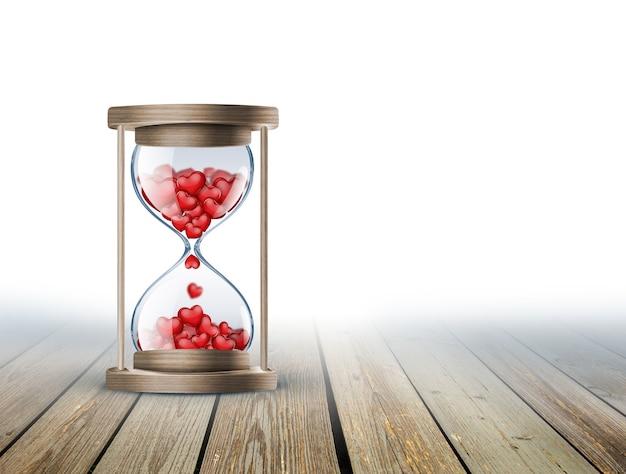 Песочные часы с красным сердцем на деревянной поверхности