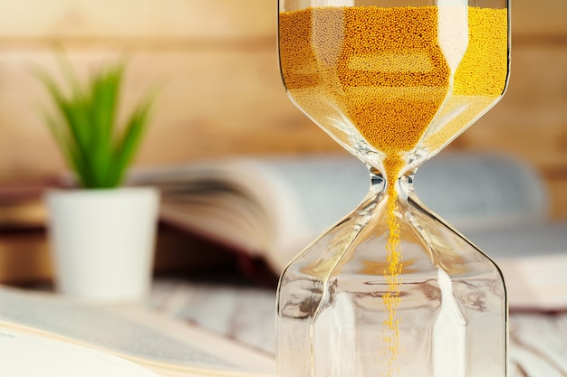 Hourglass with sand close up on wooden background