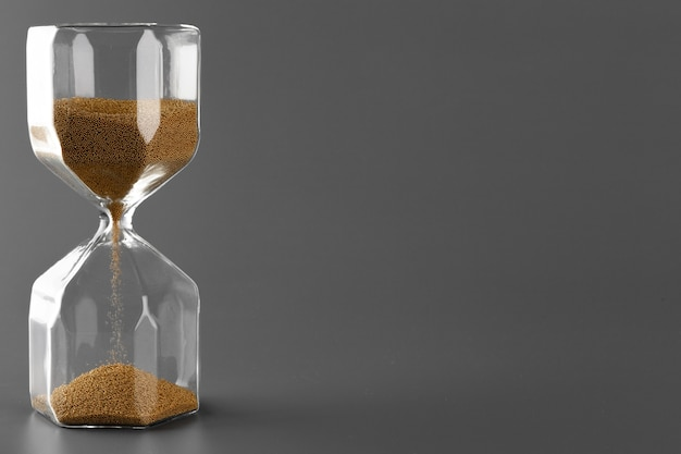 Hourglass with sand on gray close up