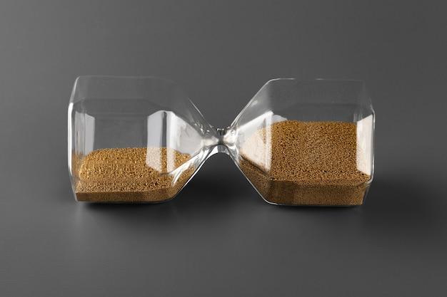 회색 바탕에 모래와 모래 시계를 닫습니다.