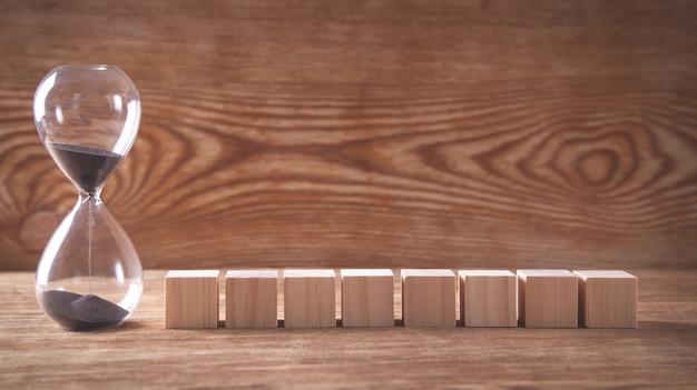 Песочные часы с деревянными кубиками на деревянных фоне.