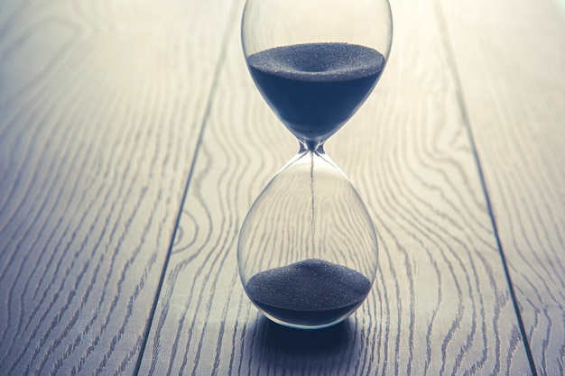 Hourglass on a wood table. time is money. business solutions in time.