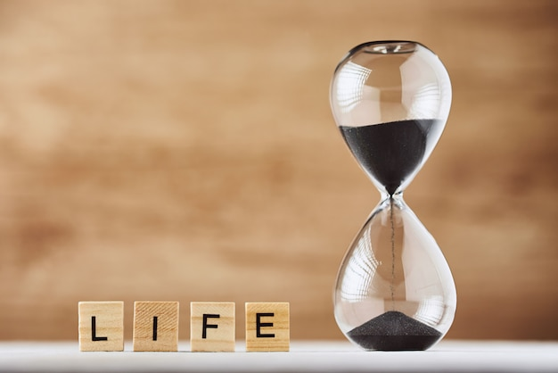 Hourglass on wood and wooden blocks with word life with copy space. concept of running out of time for life