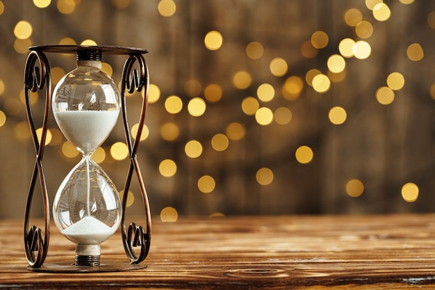 Hourglass on wooden desk against blurred lights background