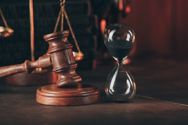 Hourglass and wooden judge gavel on table close-up
