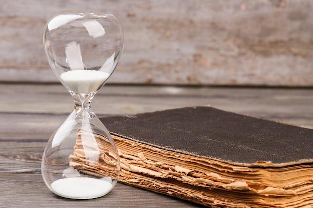 Hourglasse 및 책. 시간과 지식 개념.