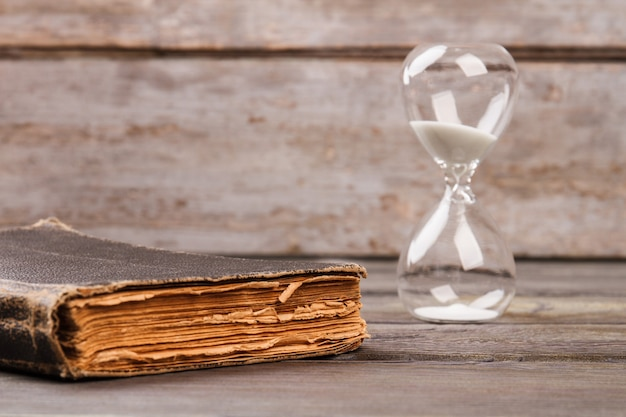 Hourglasses and old book. worn elder book and sand clock desk background.