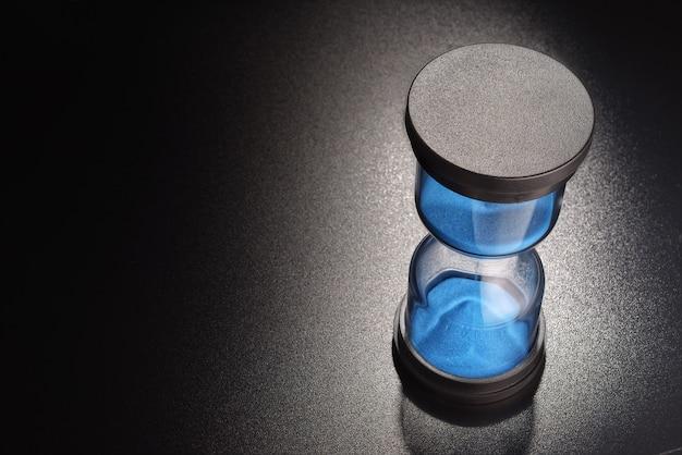 시간의 흐름을 측정하는 푸른 모래가있는 모래 시계
