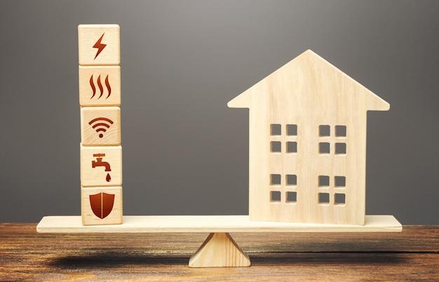 スケール上のユーティリティ公共サービスシンボルのある家とブロック。請求書の支払いの可用性。
