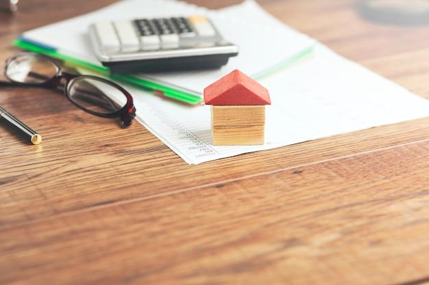 Дом и калькулятор на тетради на столе