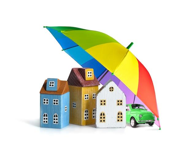 Дом и автомобиль покрыты зонтиком цвета радуги, изолированным на белом. защита собственности, концепция страховой безопасности.