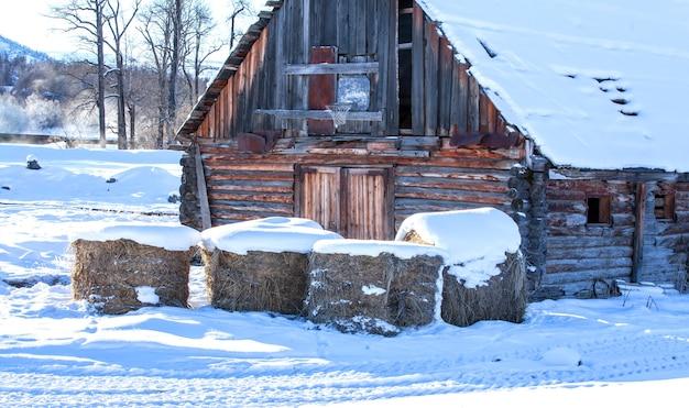冬の農場の家と干し草