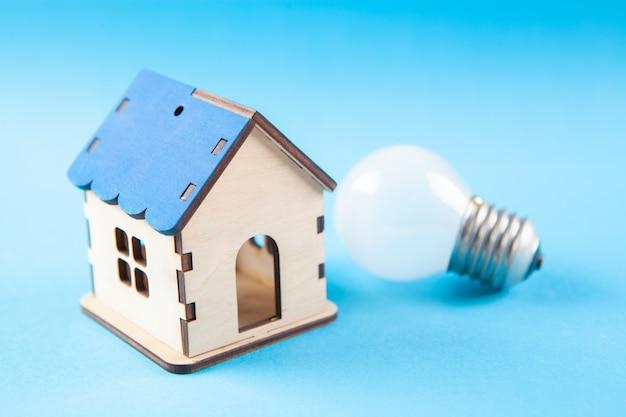 Дом и лампочка на деревянной сцене