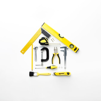 House arrangement from yellow repair tools flat lay