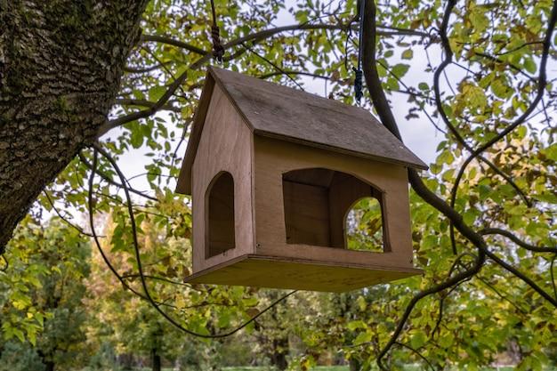 公園の木の上の家の鳥の餌箱。人々は鳥のために穀物やナッツを持ってきて注ぎます。