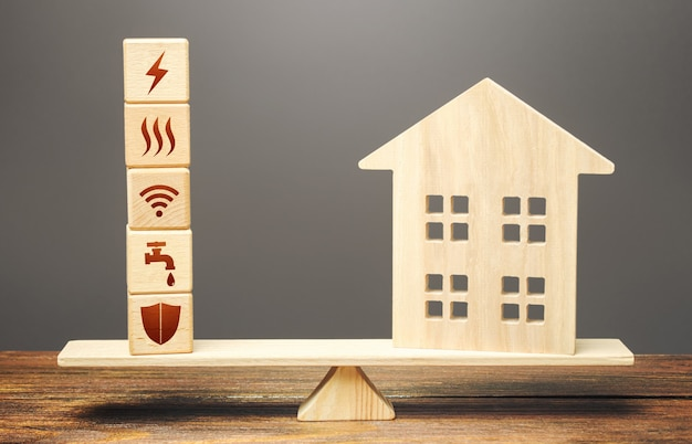 House and blocks with utilities public service symbols on scales. availability of bill payment.