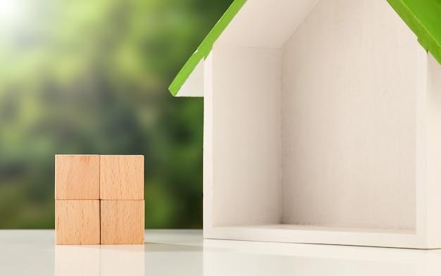 Modello della scatola della casa e cubi di legno su una superficie bianca - concetto di affari del bene immobile