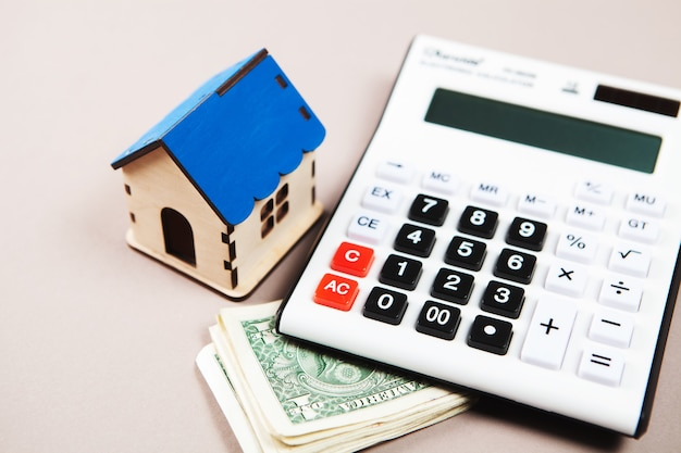 家、電卓、テーブルの上のお金。家の費用を計算するという概念