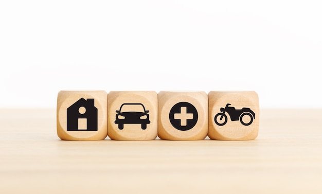 House, car, health and bike icons on wooden blocks types of insurance concept