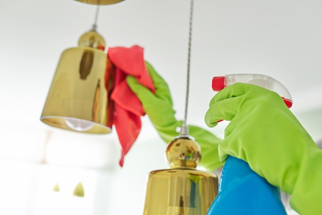 House cleaning, close-up of hands with rag detergent, cleaning and polishing lamp