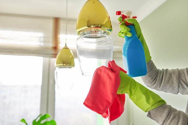 Уборка дома, крупный план рук с моющим средством для тряпки, лампа для чистки и полировки, люстра