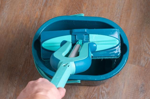 ハウスクリーニングのコンセプト。水の入ったバケツの上に青いモップを持っている女性の手、クローズアップ、上面図。