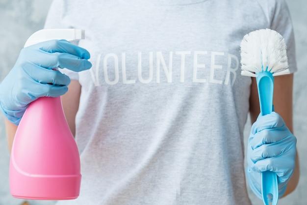ハウスクリーニングのコンセプト。ボランティアサービス。アトマイザーとブラシを備えた女性の胴体。