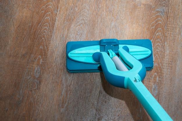 ハウスクリーニングのコンセプト。青いモップ、ウェットラミネートまたは寄木細工の床、クローズアップ、上面図で床を洗う。