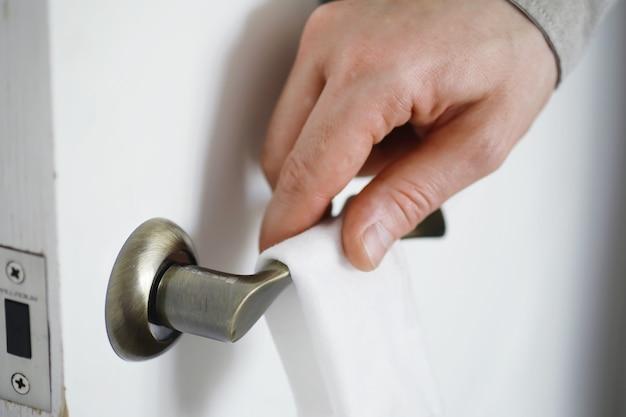 ハウスクリーニングのコンセプト。表面のほこりを拭き取ります。ドアの消毒処理はテレビの電気を処理します。自宅での検疫での衛生治療。