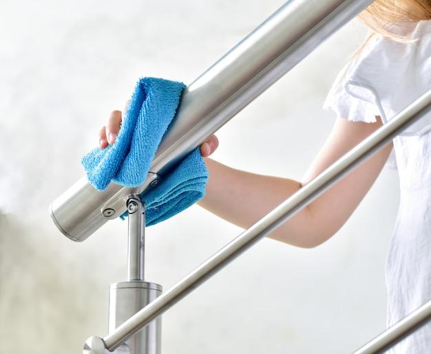 Уборка дома, маленькая девочка вытирает перила inox с голубой тряпкой