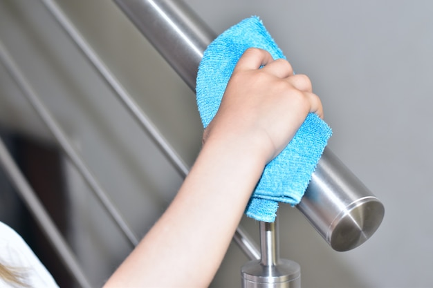 House cleaning, little girl wipes inox railing with a blue rag
