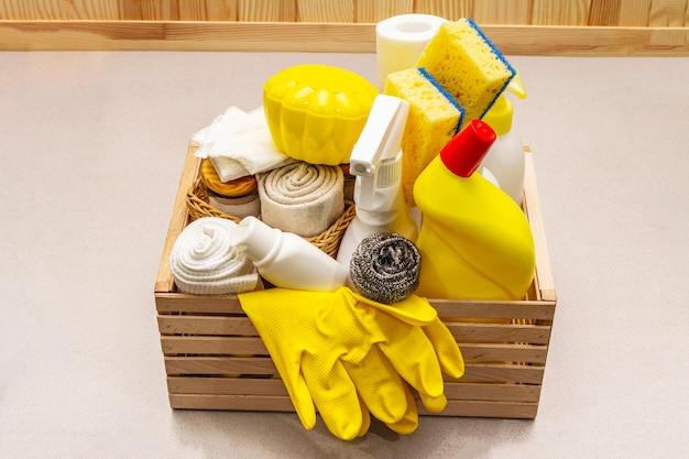 House cleaning product in wooden box. spray, bottle, gloves, dishwashing sponge, scraper, gel air freshener.