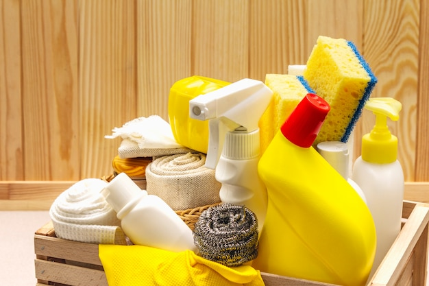 House cleaning product in wooden box. spray, bottle, gloves, dishwashing sponge, scraper, gel air freshener.