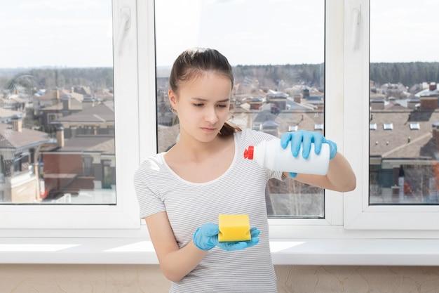Уборка дома. молодая девушка наливает чистящее средство из бутылки на губку