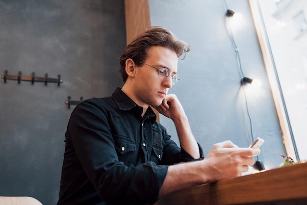 携帯電話を操作している若者のためのモダンなhouse.conceptでソファに座って、リラックスしてphone.whileを押しながら使用するソフトfocus.man
