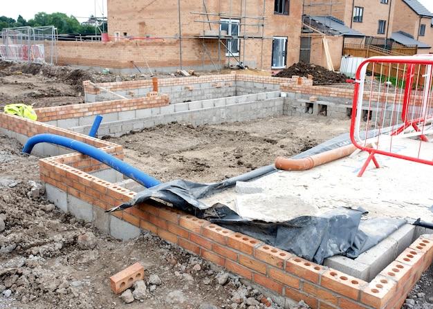 벽체의 지하 부분이 완료된 주택 개발 부지에 주택 건설이 진행 중입니다.