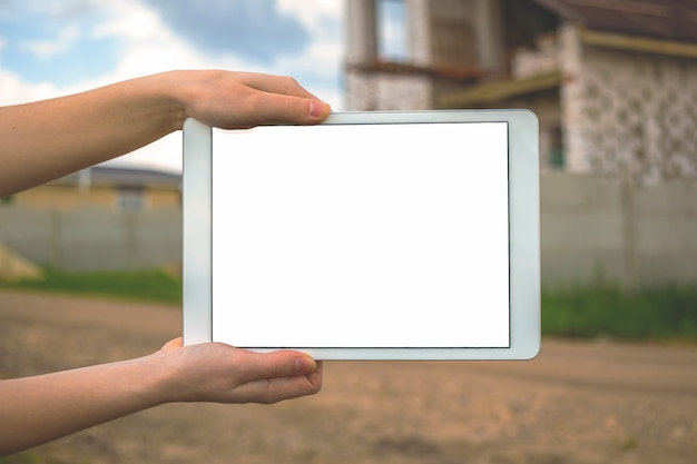 Макет строительства дома, цифровой планшет с пустым белым экраном, фон строительной площадки, концепция развития квартиры, фото с копией пространства