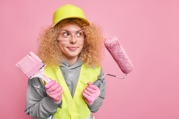 House construction and repair service. thoughtful professional woman constructor with curly bushy hair wears hardhat and transparent glasses safety helmet gloves uniform poses against pink wall