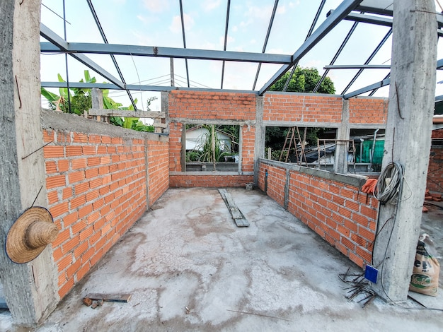 주택 건설 현장 붉은 벽돌을 벽으로 사용하십시오. 강철 지붕 프레임 콘크리트 기둥 포함.
