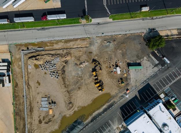 Строительные работы дома с видом на небольшую строительную площадку с большим количеством грузовиков техники нового жилого с многоквартирными домами