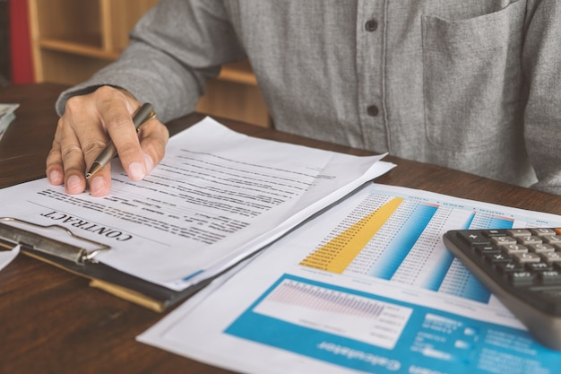 House contract, man signs a contract to purchase a home with a real estate agent