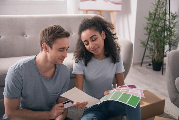 家のデザイン。家のデザインを選択しながら色を一緒に見てうれしそうな若いカップル