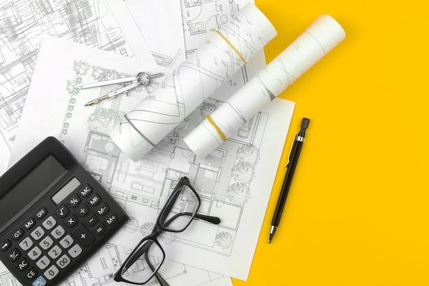 家の設計と建築計画のコンセプト。スケッチ計画の青写真をオフィスのテーブルのデスクトップに描く、上面写真